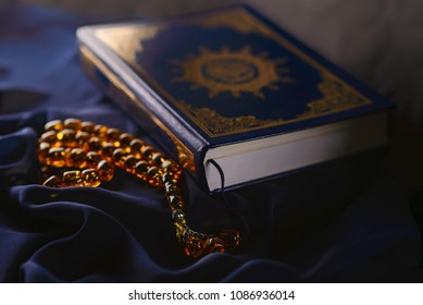 Holy islamic book Koran on the draped table with a rosary. Ramadan Kareem beautiful poster, banner, postcard for the celebration of the festival of the Muslim community