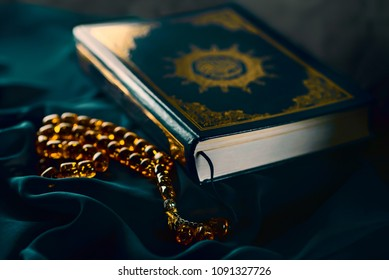 Holy islamic book Koran on the draped table with an amber rosary. Ramadan Kareem beautiful poster, banner, postcard for the celebration of the festival of the Muslim community