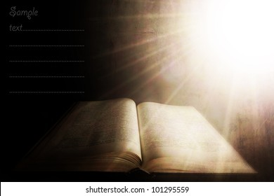holy light over the old book; vintage textured background with space for sample text