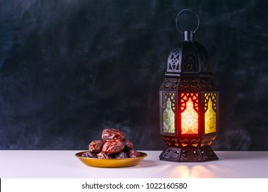 Holy month of Ramadan concept. Burning, lighting, glowing Ramadan Lantern, dates on white table on the background of a dark black gray grey textured wall. Greetings card. Place for text on the left.