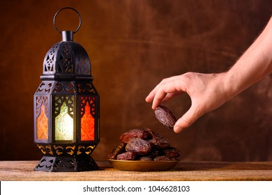 Holy month of Ramadan concept. Righteous Muslim Lifestyle. Fasting. Ramadan lantern, dates. A man's hand reaches out to a plate with dates on a wooden table. Dark brown background.