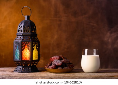 Holy month of Ramadan concept. Righteous Muslim Lifestyle. Fasting. Ramadan lantern, dates, glass of milk. Dark brown background.