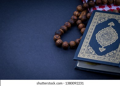Holy Quran with arabic calligraphy meaning of Al Quran and tasbih or rosary beads over black background. Selective focus and crop fragment