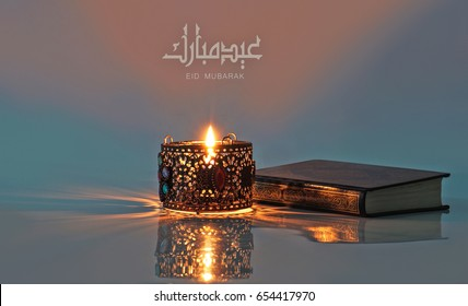 "Holy quran and lantern and Arabic nd English text of Eid Mubarak meaning ""Blessed Eid"""