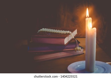 The Holy Quran and lights. Muslims holy book Koran. The Holy Quran with praying beads on wooden background. Copy space