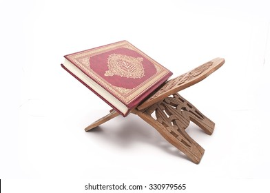 The holy Quran on a wooden book stand over white background