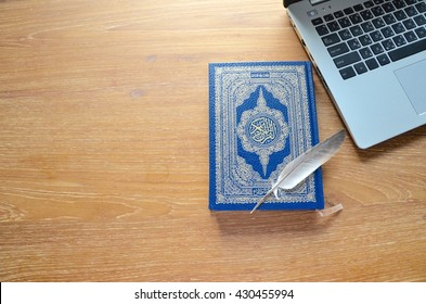 The Holy Quran(Islamic book) on wooden table - On the cover is an Arabic text : An English translation is the name of the book the Holy Quran.