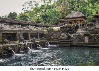 Holy spring water of sacred pool at Pura Tirta Empul Temple, Tampaksiring, Bali, Indonesia.