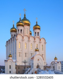 Holy Trinity Cathedral. Large Orthodox Church. Beautiful white building with golden domes and crosses against a blue sky. Cold winter. Magadan, Siberia, Far East of Russia.
