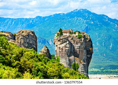 Holy Trinity Monastery on a top of the rock on the mountain range background.  Meteora, Greece.