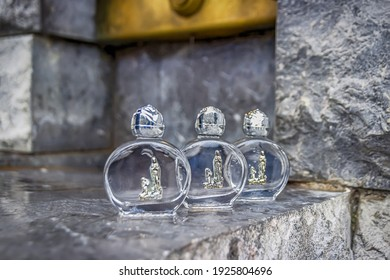 Holy water in a small bottles near a source. Lourdes France
