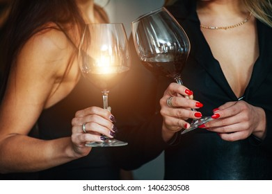 Holyday and rest. Female friends celebrating with wine in a bar and toasting with glasses of wine.