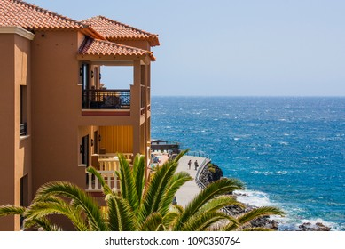 Holyday summer time. Orange hotel building near beautiful blue sea ocean coastline. Two people walking  along the beach road. Blue sky, ocean waves, green palms, orange building