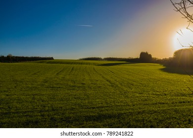 Holywood, County Down / Northern Ireland - 01.07.2018 Rolling Green Fields with plane flying towards the sunshine