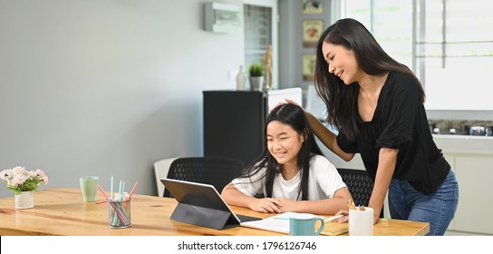 Home activity concept, Mother is teaching a daughter to do homework at home.