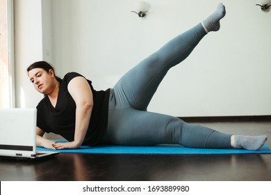 Home activity and training, online fitness class. Overweight woman exercising under the supervision of a personal trainer or watching video guide using laptop in living room