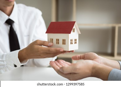 Home agents are giving house gifts to new home buyers in office room.