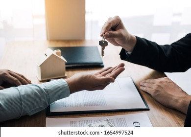 Home agents are handing out keys to home buyers who are signing contracts at the office.