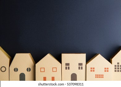 Home architectural model paper box cubes on black background with copy space.Real estate concept.