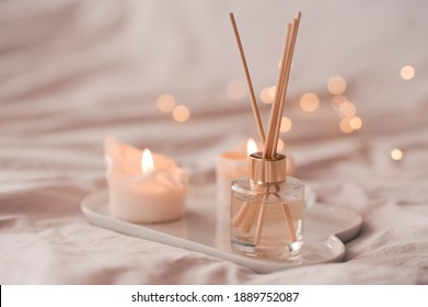 Home aroma fragrance diffuser with burning candles on white tray in bed over glowing lights close up. Cozy atmosphere. Wellness. Healthy lifestyle.