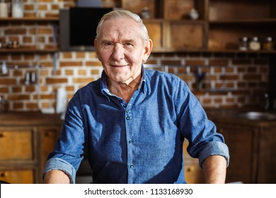 Home atmosphere. Pleasant elderly man resting in the kitchen while looking in the camera