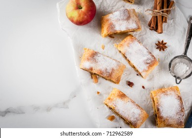Home autumn, summer baking, puff pastries. Apple strudel with nuts, raisins, cinnamon and powdered sugar. On white marble table. Sliced, with ingredients. Copy space top view