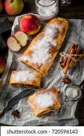 Home autumn, summer baking, puff pastries. Apple strudel with nuts, raisins, cinnamon and powdered sugar. On a wooden old rustic table. Sliced, with ingredients. Copy space top view