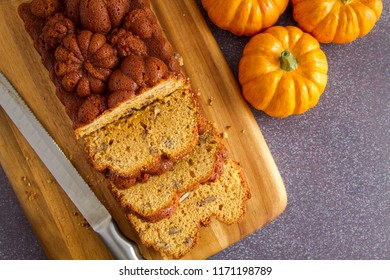 Home baked loaf of pecan pumpkin bread sitting on wooden cutting board with knife shot from above and space for text