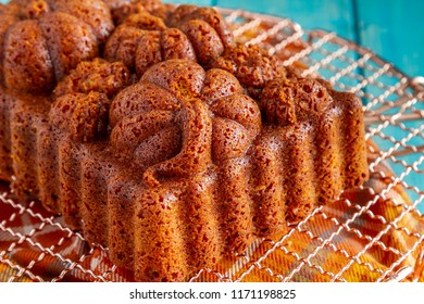 Home baked loaf of pecan pumpkin bread baked in decorative fall themed pan sitting on copper cooling rack on blue wooden table
