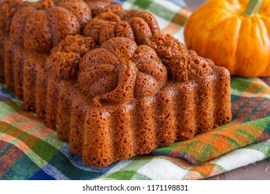 Home baked loaf of pumpkin bread baked in decorative fall themed pan sitting on plaid towel with small pumpkin in background