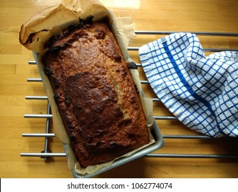 Home baked organic vegan banana bread cake loaf fresh cooked warm from oven in tin with grease proof lined paper on metal cooking rack with tea towel against wood kitchen surface background