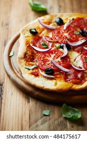 Home baked pizza with tomatoes, mozzarella, red onion, salami, black olives and fresh basil. Italian pizza. Home made food. Concept for a tasty and hearty meal. Rustick wooden background.