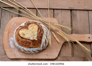 Home baked spelt bread with spelt flakes and sunflower seeds and hand scoring in a shape of heart; crusty sourdough loaf of wheat bread with spelt flour on wooden board with wheat ears in background