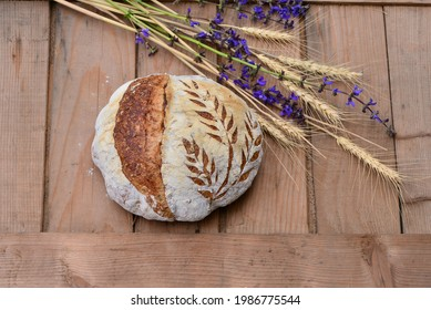Home baked spelt bread with spelt flakes and sunflower seeds on wooden boards; crusty sourdough loaf of wheat bread with spelt flour with bouquet of summer flowers and wheat ears in background