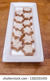 Home baked Swiss or German style cinnamon star shaped Christmas cookies known as Zimtsterne on white platter with rustic wooden background