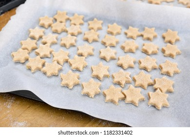 Home baking Christmas cookies: star shaped biscuits arranged on baking sheet with paper on messy kitchen bench with sugar