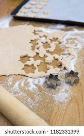 Home baking star shaped Christmas cookies, with rolling pin, biscuit cutters, dough, sugar and baking sheet with paper on wooden kitchen counter