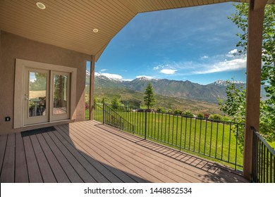 Home balcony with glass access door and stairs that leads to the grassy yard