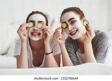 Home beauty saloon. Conception of skin care by using fresh cucumber rings and white mask on the face. Two female sisters have weekend at bedroom.