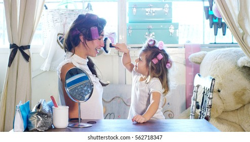 At home, in the bedroom, mother and daughter play to put on makeup, combing hair together. The mother and daughter smiling as they try beauty tricks. Concept: beauty, family, fun, memories.