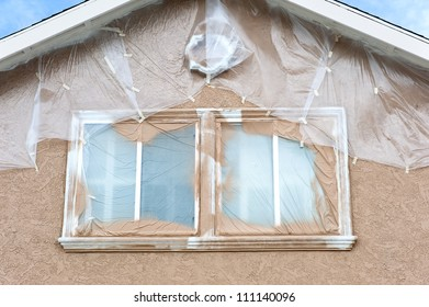 A home is being repainted and is painstakenly masked with plastic sheeting to protect areas from paint overspray during a remodeling project.