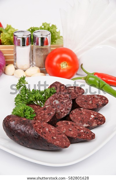 Home blood sausage on a white plate with fennel, parsley and lettuce