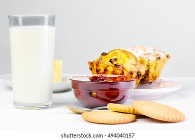 Home breakfast food & drink healthy lifestyle concept: Healthy homemade breakfast. Milk, jam & bakery.  Milk, biscuit, jam, cake & cookie. White linen tablecloths Light background