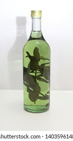 Home Brew Brandy With Green Herbs in Bottle