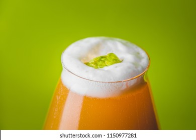 Home brewed Juicy and Hazy NEIPA Hop Bomb Beer over Green Background