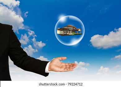 Home in bubble over business man hand against  blue sky
