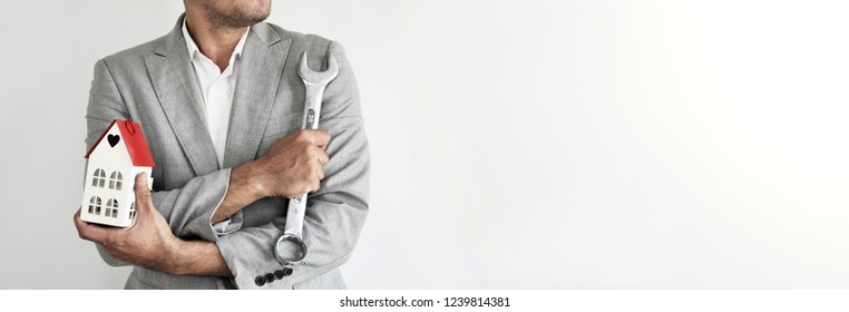 Home Builder. Engineering and Architect. Man on grey suit. Man holding wrench on grey background with copy space. Strong, Professional man, Civil construction worker, Designer.