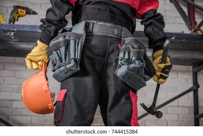 Home Building Contractor Preparing For the Job. Safety Helmet in Left Hand and Hammer in the Right.