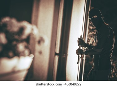Home Burglar in a Mask Breaking Into the House. House Thief Concept Photo.