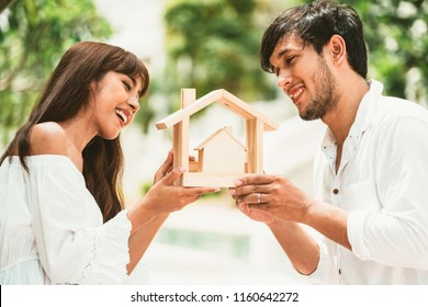 Home buyers concept. - Young married couple holding wooden home model to show the meaning of home buyers making decision.